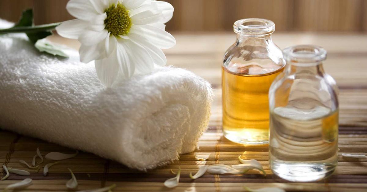 esencialne oleje na stole s uterakom a kvetinou
